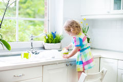Little curly toddler girl in colorful dress washing dishes Royalty Free Stock Images