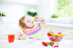 Little curly toddler girl having breakfast drinking juice Stock Images