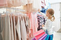 Little customer standing in store and choosing new dresses. View from side of lovely little customer standing in store and choosing new dresses. Funny girl royalty free stock image