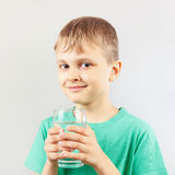 Little cut boy with glass of mineral water Stock Photos