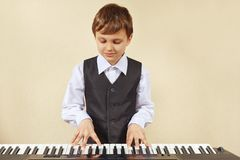 Little cut boy play the keys of electronic piano. Little cut boy play the keys of the electronic piano Royalty Free Stock Image