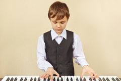Little cut boy play the keys of synthesizer Royalty Free Stock Image