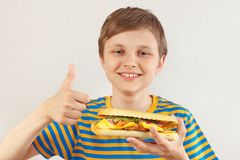Little cut boy recommends and likes tasty cheeseburger on white background royalty free stock image