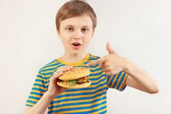 Little cut boy recommends tasty hamburger on white background stock images