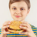 Little cut boy in a striped shirt with a tasty hamburger on white background stock photos