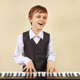 Little cut boy in suit playing the digital piano Stock Images