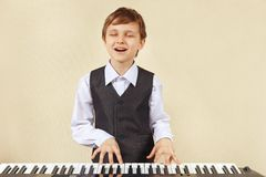 Little cut boy in suit playing the electronic organ Stock Photos
