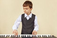 Little cut boy in suit playing the electronic synth Royalty Free Stock Photography