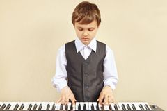 Little cut boy in suit playing the electronic synthesizer Royalty Free Stock Photo