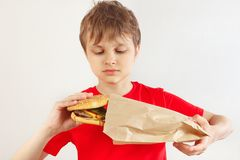 Little cut boy take out a big hamburger from a package on white background stock images