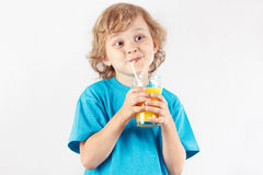 Little cut child drinking a fresh citrus juice on white background Royalty Free Stock Photos