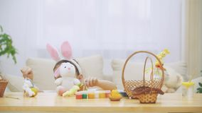 Little cute and adorable girl is smiling and playing with colorful chicken`s eggs and bunnies. Concept Easter holiday. stock video