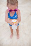 Little cute adorable girl in swimsuit rubs Royalty Free Stock Photos