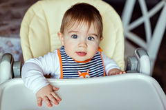 Little cute adorable toddler boy striped bib sits in chair and l royalty free stock image