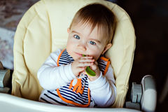 Little cute adorable toddler boy striped bib sits in a high chai Stock Photos