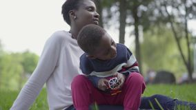 Little cute African American boy playing with plastic toy in the park, sitting on mother`s laps close up. The woman and. Little cute African American boy playing stock footage