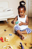 Little cute african american girl playing with animal toys at ho Stock Images