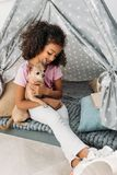 Little cute african american kid with chihuahua dog in teepee. At home royalty free stock photos