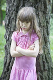 Little cute angry girl seven years. Old standing at oaklll stock image