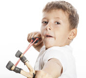 Little cute angry real boy with slingshot. Close up stock photography