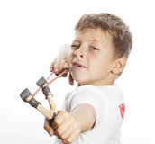 Little cute angry real boy with slingshot isolated. On white background close up stock photography