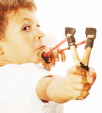 Little cute angry real boy with slingshot isolated. On white background close up royalty free stock image