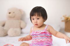 Little cute asian baby girl sitting on bed playing Royalty Free Stock Photo