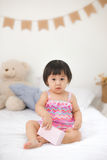 Little cute asian baby girl sitting on bed playing Royalty Free Stock Images