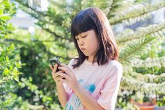 Asian kid girl using smartphone device play game. Little cute asian kid girl in pink t-shirt looking at device and using wireless smartphone send message, play royalty free stock image