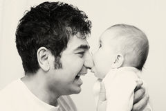 Father and his son. Little cute baby biting nose of his father Stock Images