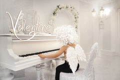 Little cute baby boy angel with wings, Cupid, Valentine`s piano. Little cute baby boy beautiful angel with wings, Cupid, Valentine`s piano Stock Image
