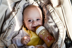 Little cute baby boy. Close up portrait of little cute smiling baby boy in a carriage drinking from feeding bottle royalty free stock photo