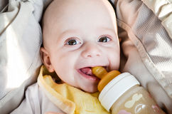 Little cute baby boy. Close up portrait of little cute smiling baby boy in a carriage drinking from feeding bottle royalty free stock photos