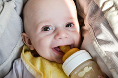 Little cute baby boy. Close up portrait of little cute smiling baby boy in a carriage drinking from feeding bottle stock image