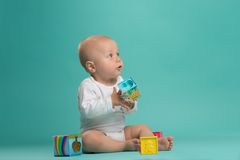 Little cute baby boy playing with color blocks Stock Photos