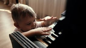 Little cute baby boy with smile on his face knock on piano keys in slow motion stock video
