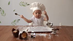 Little cute baby in a chef`s cap knocks with cutlery on a wooden table stock video