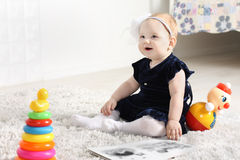 Little cute baby in dress sits on soft carpet Royalty Free Stock Image