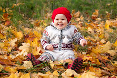 Little cute baby girl on a background of autumn leaves.  Royalty Free Stock Photography