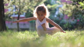 Little cute baby girl doing yoga exercise on the grass in park.