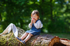 Little cute baby girl eating fruit in forest Royalty Free Stock Photography