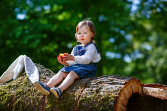 Little cute baby girl eating fruit in forest Stock Photography