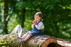 Little cute baby girl eating fruit in forest Royalty Free Stock Images