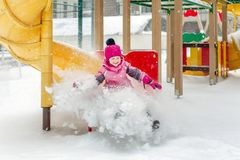 Little cute baby girl having fun on playground at winter. Children winter sport and leisure outdoor activities.  stock image