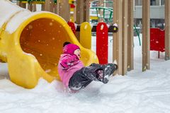 Little cute baby girl having fun on playground at winter. Children winter sport and leisure outdoor activities.  royalty free stock photography