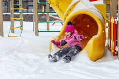 Little cute baby girl having fun on playground at winter. Children winter sport and leisure outdoor activities.  royalty free stock images