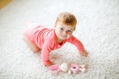 Little cute baby girl learning to crawl. Healthy child crawling in kids room with colorful toys. Back view of baby legs. Cute toddler discovering home and stock photo