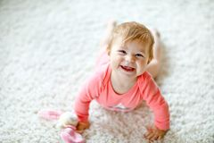 Little cute baby girl learning to crawl. Healthy child crawling in kids room with colorful toys. Back view of baby legs royalty free stock photo