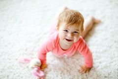 Little cute baby girl learning to crawl. Healthy child crawling in kids room with colorful toys. Back view of baby legs royalty free stock images