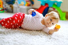 Little cute baby girl learning to crawl. Healthy child crawling in kids room with colorful toys. Back view of baby legs. Cute toddler discovering home and royalty free stock images
